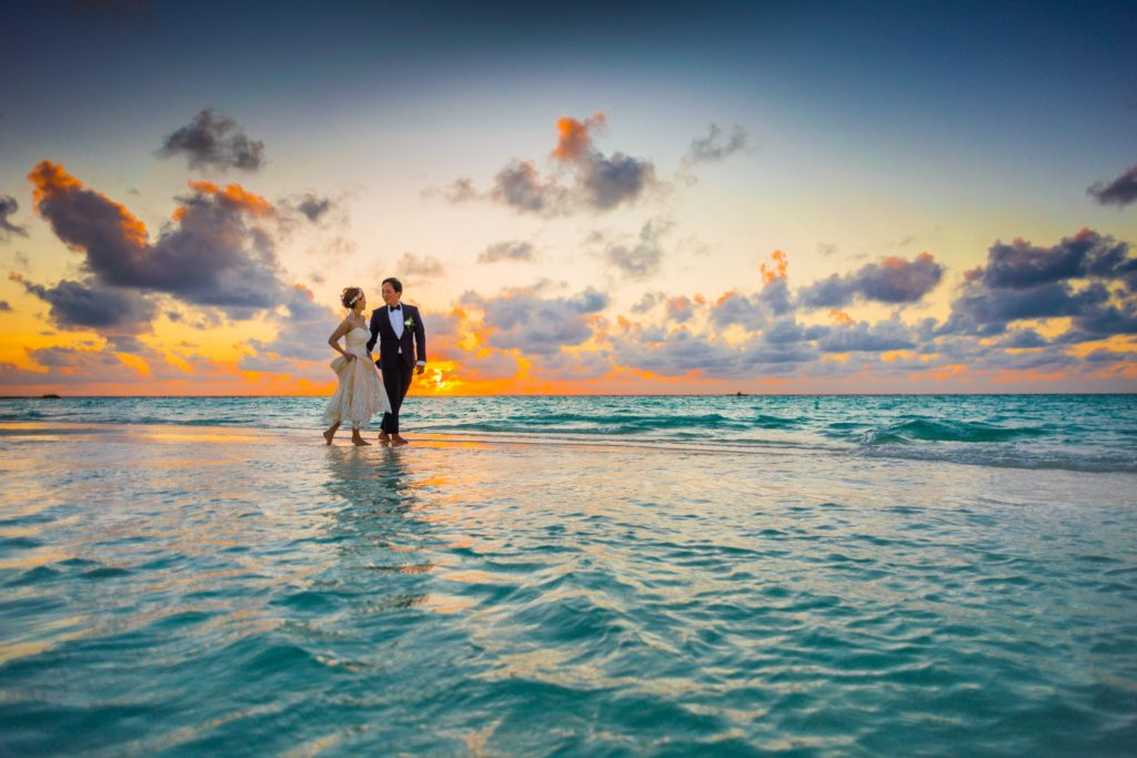 Bride and Groom walking on a beach at sea Wedding Day