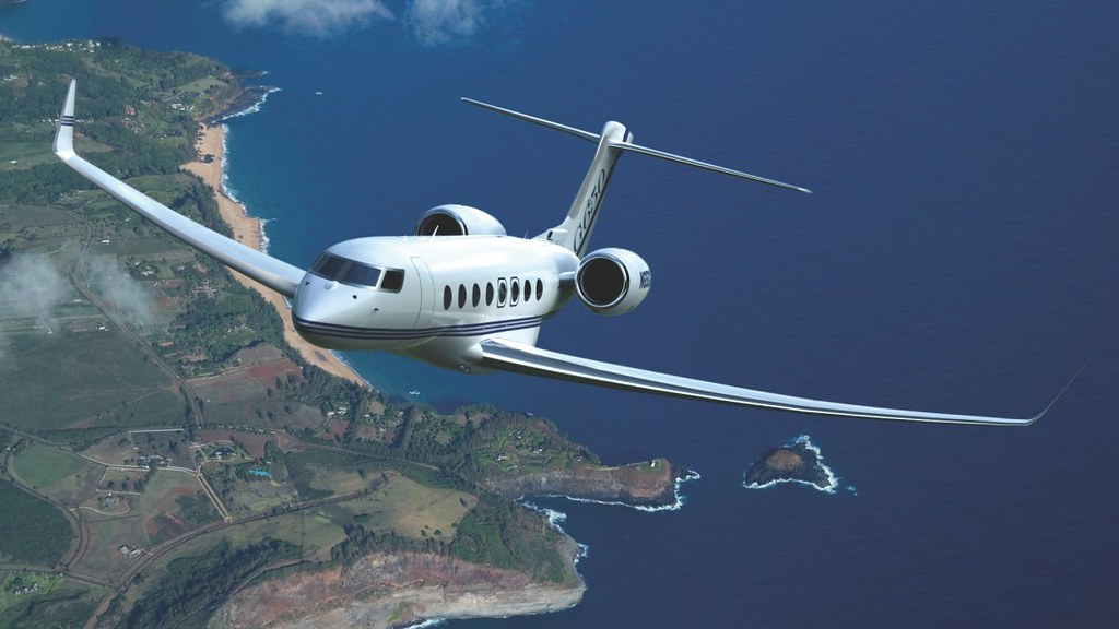Private jet Gulfstream G650 is flying above ocean