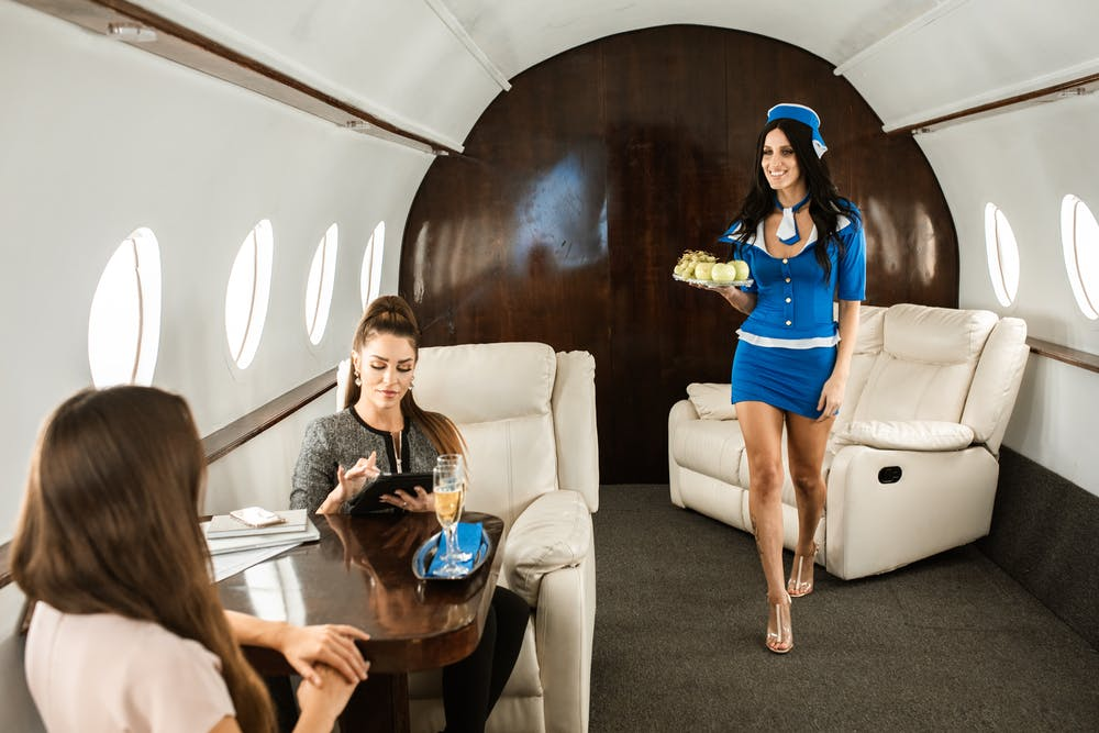women in blue shirt serving in private jet