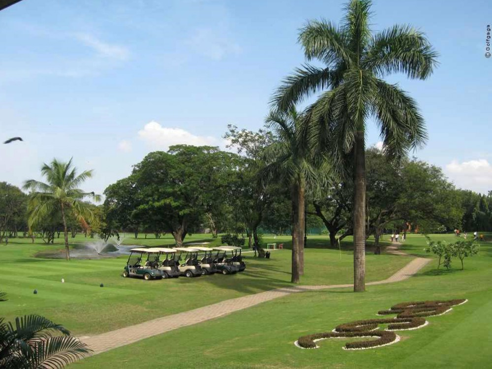 Golf carts parked in plush green field Bombay Presidency Golf Course