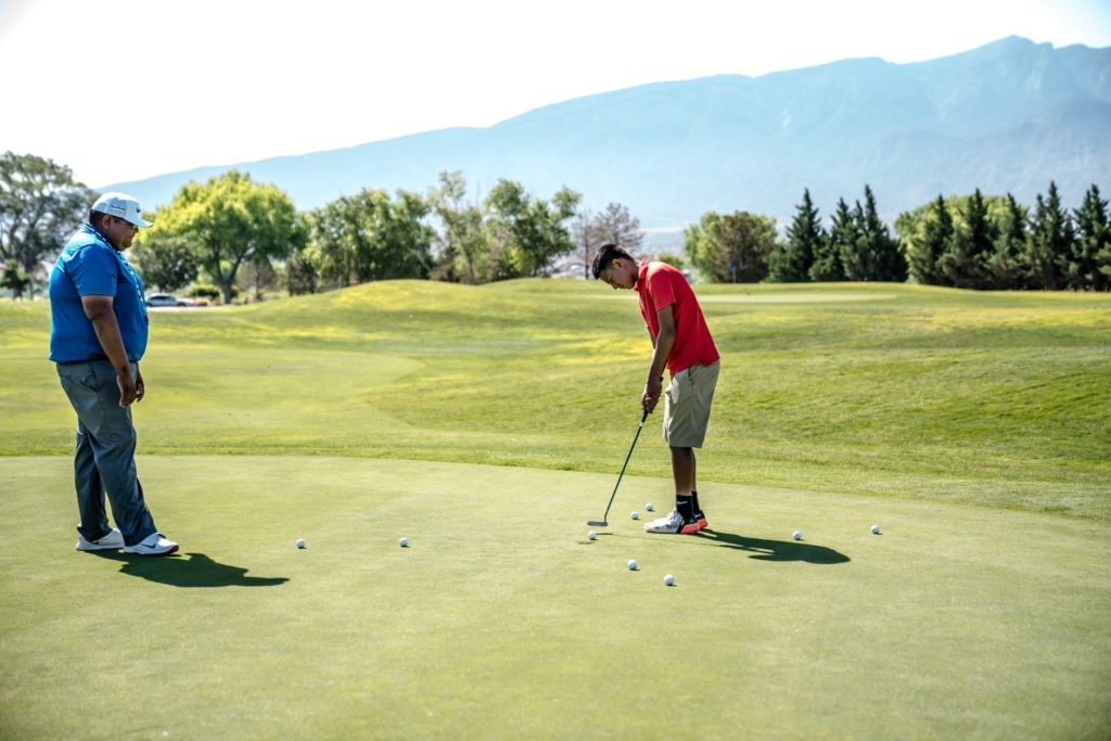 A male golfer in red tee-shirt aiming at golf ball with a stick in Kashmir Golf Club